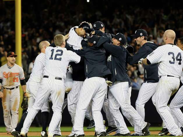 Derek Jeter of the New York Yankees is joined by teamates after driving in the game-winning run  on his final game at Yankee Stadium in the Bronx, New York, Thursday night, Sept. 25, 2014. The Yankees beat Baltimore, 3-2.  (Michelle V. Agins/The New York Times)  ORG XMIT: NYT4 Photo: MICHELLE V. AGINS / NYTNS