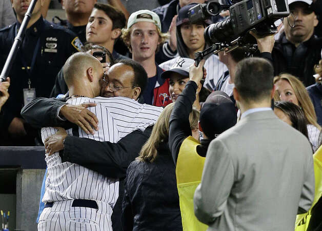 New York Yankees shortstop Derek Jeter hugs his father, Sanderson Jeter, after playing his last home career baseball game at Yankee Stadium, Thursday, Sept. 25, 2014, in New York. Jeter drove in the winning run in the ninth inning against the Baltimore Orioles to propel the Yankees to a 6-5 win. (AP Photo/Julie Jacobson) ORG XMIT: NYJJ174 Photo: Julie Jacobson / AP