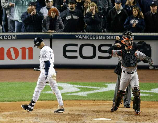 New York Yankees' Derek Jeter walks back to the dugout as Baltimore Orioles catcher Caleb Joseph throws the ball to third after Jeter struck out in the fifth inning of a baseball game, Thursday, Sept. 25, 2014, in New York. (AP Photo/Bill Kostroun)  ORG XMIT: NYJJ142 Photo: Bill Kostroun / AP