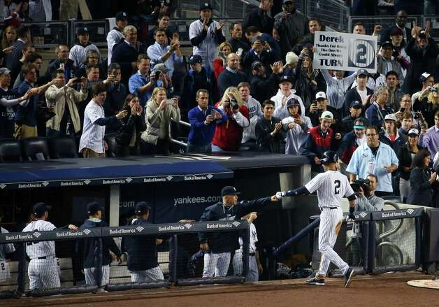 New York Yankees shortstop Derek Jeter receives congratulations from the dugout after scoring in his final home game at Yankee Stadium, Sept. 25, 2014. With the Yankees mathematically eliminated from the playoffs, the season home finale was a rainy and emotional goodbye to Jeter, retiring after 20 seasons with the club. (Chang W. Lee/The New York Times) ORG XMIT: XNYT201 Photo: CHANG W. LEE / NYTNS