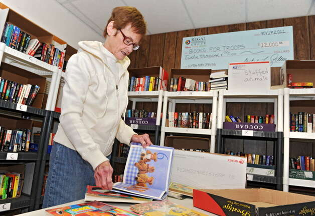 Ellen Keegan, of Books for Troops, goes through donated children's books at Old Halfmoon Town Hall in 2013. She said this week that some people are dumping smelly and unwanted books at some of their sites. (Lori Van Buren / Times Union)