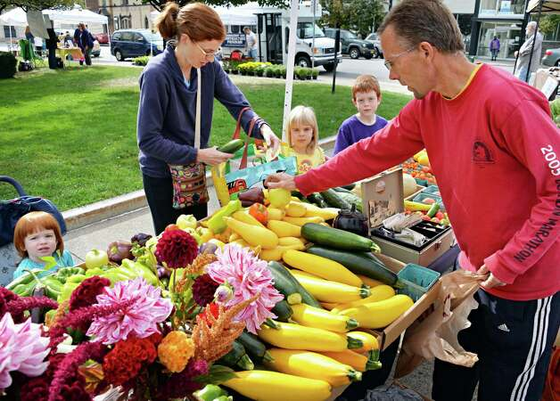 Janet Makham of Glenville and children, Adele, 1, left, Camille, 5, and Kyle, 7, buy fresh vegetables from Fort Hunter Farms' Brian DeBracci, right, at the Shenectady Farmers' Market at City Hall Thursday Sept. 25, 2014, in Schenectady, NY.  (John Carl D'Annibale / Times Union) Photo: John Carl D'Annibale, Albany Times Union