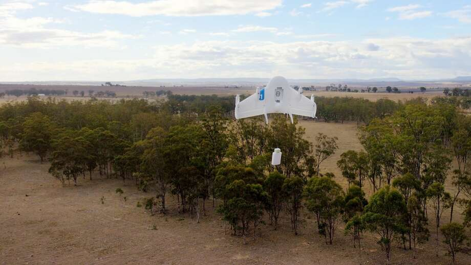 """In this image released by Google, a drone lowers a package to the ground in Queensland, Australia. The company is testing using drones to deliver items bought online. Two years of research into what Google referred to as """"Project Wing"""" was capped last month with test flights delivering candy, water, medicine, dog treats and cattle vaccine. Photo: -, AFP/Getty Images"""