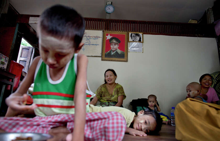 In this Aug. 27, 2014 photo, a portrait of General Aung San, an independence hero and father of Myanmar's opposition leader Suu Key, is displayed on the wall of the National League for Democracy's HIV/AIDS prevention and caring center as patients infected with HIV and their family members rest in South Dagon, outskirts of Yangon, Myanmar. Patients from throughout the country take residence in the center for three months to receive Anti-Retroviral Therapy (ART) regularly. (AP Photo/Gemunu Amarasinghe) Photo: Gemunu Amarasinghe / Associated Press / AP