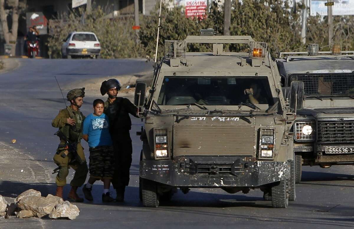 Israeli forces detain a Palestinian boy amid protest of the Israeli settlement Ofra's expansion.