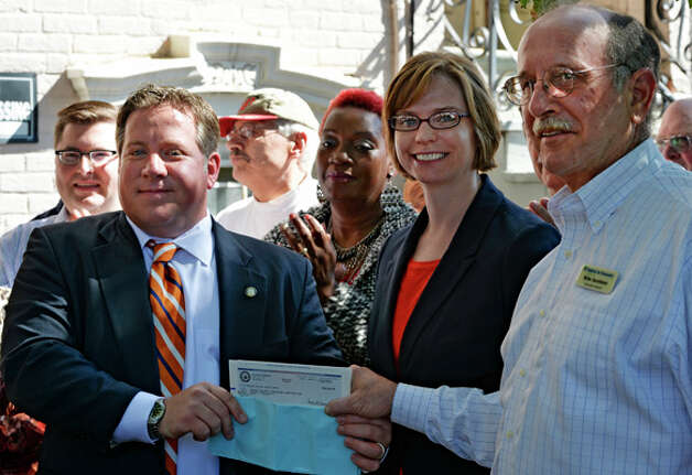 New executive director of the Land Bank Corporation Katie Bronson, center and Mike Jacobson, chairman, of the Albany County Land Bank Corporation, right receive a $500,000 check from Albany County Executive Dan McCoy, left,  during a press conference held Friday morning Sept. 26, 2014 in front of 543 Clinton Avenue in Albany, N.Y.   (Skip Dickstein/Times Union) Photo: SKIP DICKSTEIN, ALBANY TIMES UNION / 00028769A