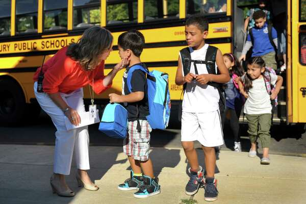 Leandro Pacheco, 5, talks with principal Dr. Anna Rocco as he arrives at school for the first day of classes in August at Ellsworth Avenue School in Danbury. Danbury school officials have added three extra buses to make sure that school children aren't riding on a bus too long.