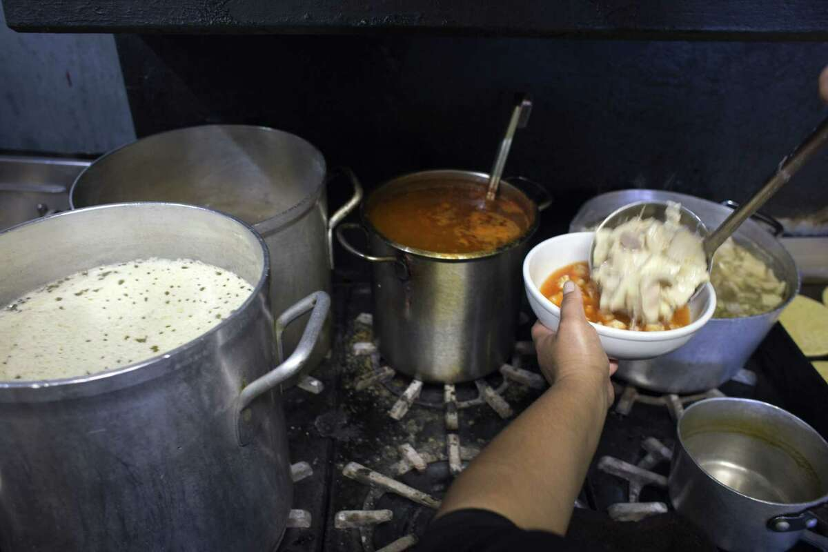 Margarita Lopez ladles Menudo into a bowl to be served to a customer of Taqueria Campos in the Fruitvale District of Oakland. It is well known for Jalisco style cooking and specializes in Menudo, Pozole, and Birria.