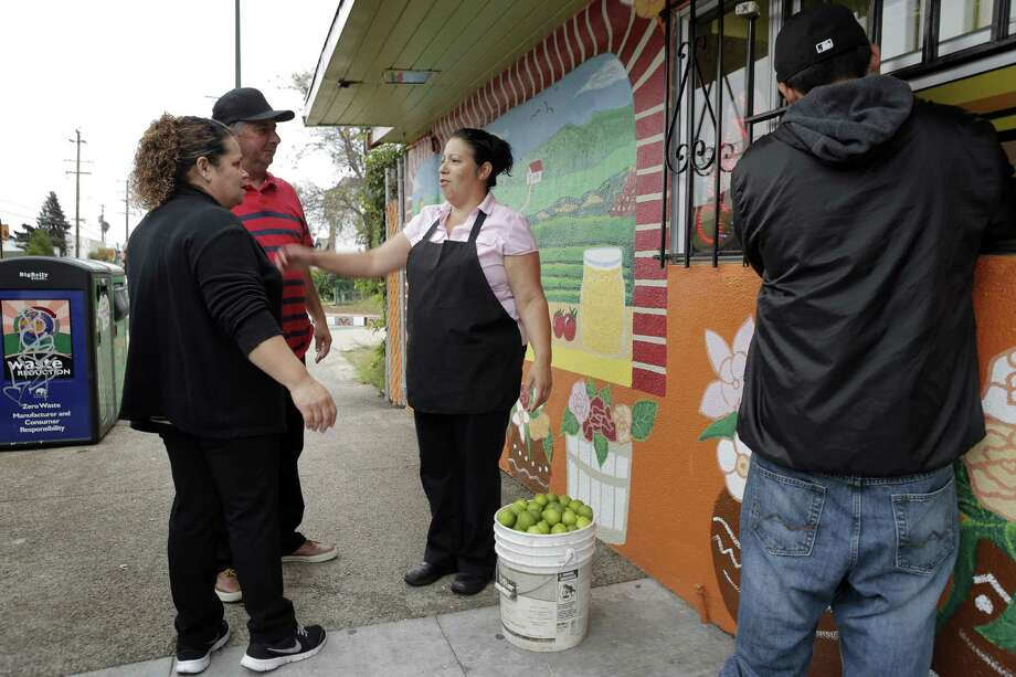 Ana Maria Campos (center) greets her friends Maria and Ignacio Zepeda as they drop off a bucket of fresh lemons at Taqueria Campos in the Fruitvale district of Oakland. Photo: Carlos Avila Gonzalez, Staff Photographer / The Chronicle / ONLINE_YES