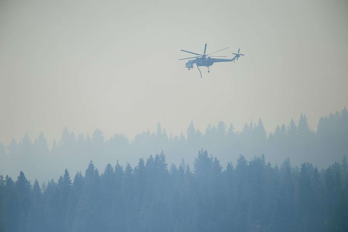 In this Wednesday, Sept. 24, 2014 photo, smoke from the King Fire fills the air as a helicopter prepares to refill with water near the Union Valley Reservoir in El Dorado County, Calif. Heavy rains this week and the prospect of more wet weather over the weekend are raising hopes that firefighters will get full containment quickly on the massive wildfire in a heavily forested region of the Sierra east of Sacramento. (AP Photo/The Sacramento Bee, Randall Benton)