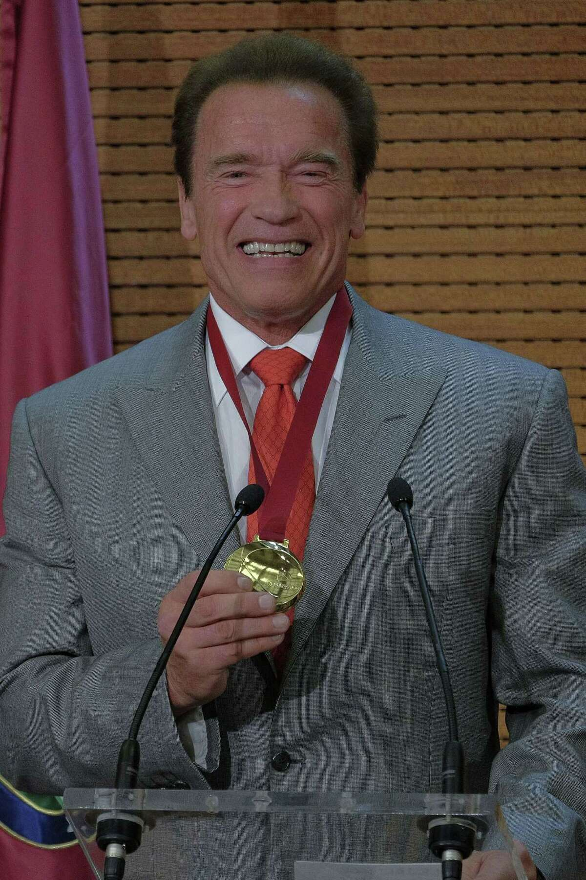 US actor Arnold Schwarzenegger poses with the medal of Tourist Ambassador for Madrid for his contribution to the promotion of the city in Madrid on September 26, 2014.