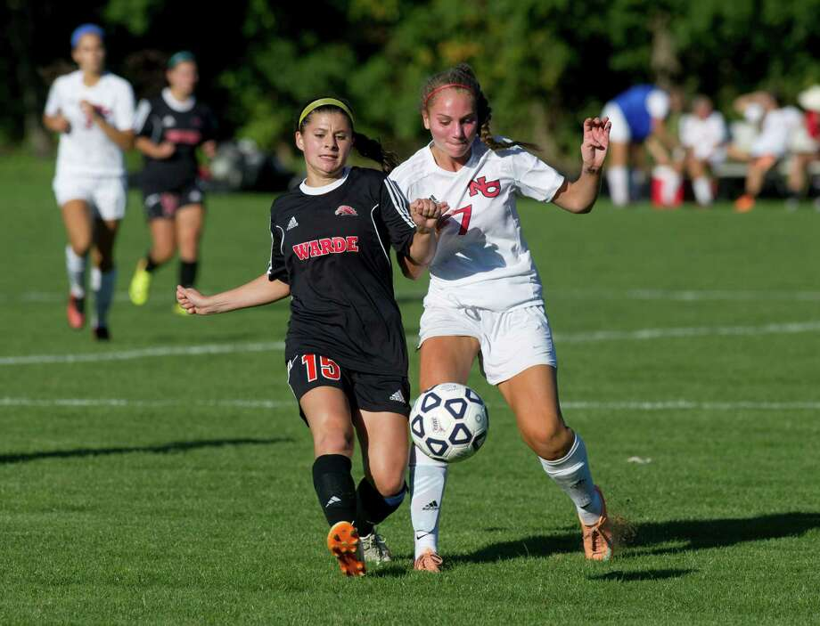 Fairfield Warde's Julia Andrews, left, and New Canaan's Abigail Farley, right, compete for control of the ball during Friday's girls soccer game in New Canaan, Conn., on September 26, 2014. Photo: Lindsay Perry / Stamford Advocate