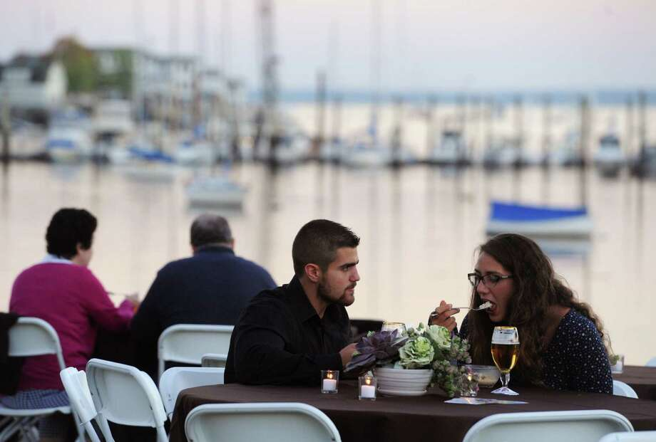 Johnnie Chiapperino, of Norwalk, and Alicia Andrianus, of Darien, enjoy shrimp and grits with a glass of wine as the sun sets in front of Greenwich Harbor at day two of the Greenwich Wine + Food Festival at Roger Sherman Baldwin Park in Greenwich, Conn. Friday, Sept. 26, 2014.  Friday night's festivities included the 2014 Most Innovative Chefs Gala featuring special guest culinary masters Geoffrey Zakarian and Jean-Georges.  The night concluded with a performance by southern classic rock band The Marshall Tucker Band.  The festival continues Saturday starting at noon, with live music featuring Alabama from 6:30 to 10 p.m. Photo: Tyler Sizemore / The News-Times