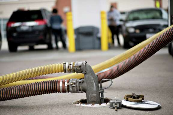 Customers fill up vehicles beyond a filler hose as 7,500 gallons of unleaded gasoline are delivered to a Shell station in Peoria, Illinois, U.S., on Friday, Sept. 12, 2014. (Photographer: Daniel Acker/Bloomberg)
