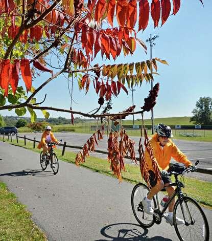 Sue, left, and Dan Elmendorf of Colonie bike past fall foliage in Blatnick Park Friday Sept. 26, 2014, in Niskayuna, N.Y.  (John Carl D'Annibale / Times Union) Photo: John Carl D'Annibale