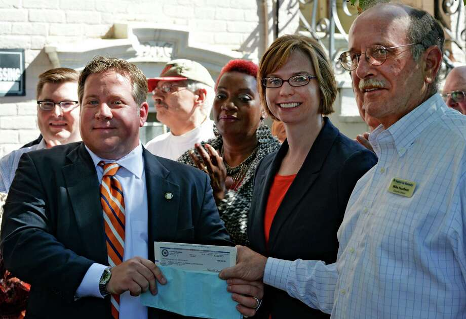 New executive director of the Land Bank Corporation, Katie Bronson, center, and Mike Jacobson, chairman of the Albany County Land Bank Corporation, right, receive a $500,000 check from Albany County Executive Dan McCoy, left, during a press conference held Friday morning, Sept. 26, 2014, in front of 543 Clinton Avenue in Albany, N.Y.  Albany County, which has pledged another $500,000 funding next year, recently transferred 83 properties ? about half of them buildings, half vacant land ? to the land bank. (Skip Dickstein/Times Union) Photo: SKIP DICKSTEIN / 00028769A