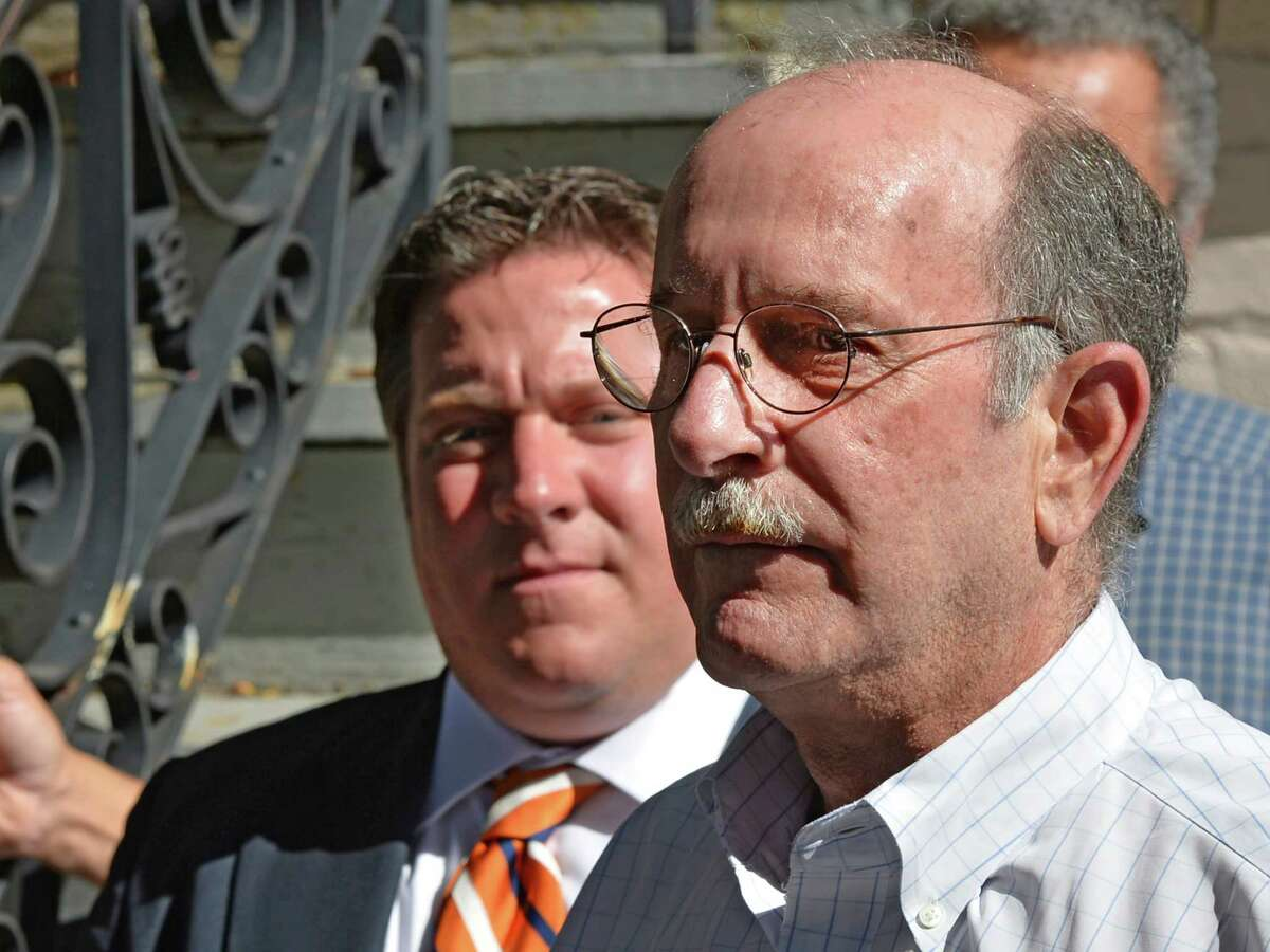 Mike Jacobson, chairman of the Albany County Land Bank Corporation, speaks as Albany County Executive Dan McCoy, background, listens during a press conference Friday morning, Sept. 26, 2014, in front of 543 Clinton Avenue in Albany, N.Y. During the press conference a $500,000 check was given to the Land Bank by Albany County Executive Dan McCoy as well as the naming of the new Land Bank executive director Katie Bronson. Albany County, which has pledged another $500,000 funding next year, recently transferred 83 properties ? about half of them buildings, half vacant land ? to the land bank. (Skip Dickstein/Times Union)