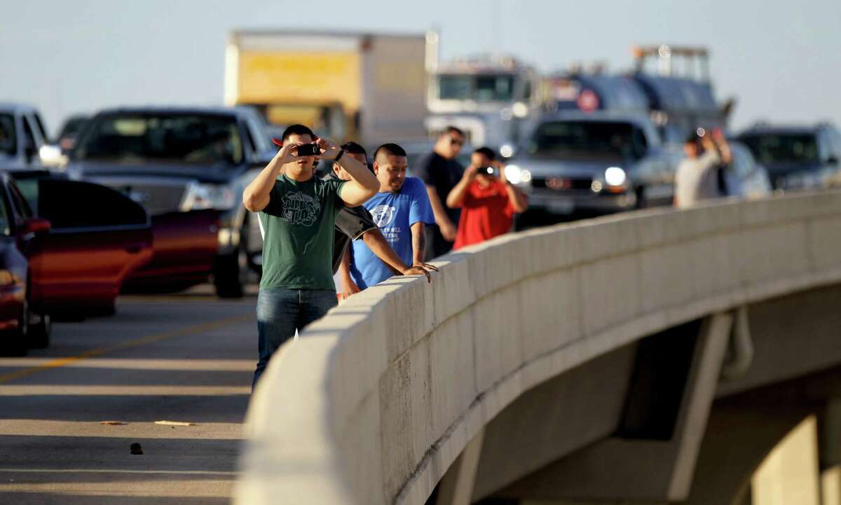 With traffic going nowhere, drivers leave their vehicles to take photos as the Houston Fire Department responds to the truck fire that caused so much trouble Friday morning on the West Loop. Despite the flames and roiling smoke, no injuries were reported.