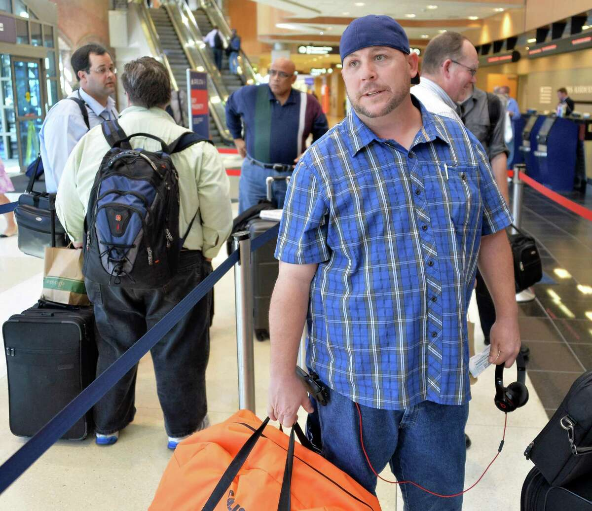 Stranded traveler Brian Campbell of Phoenix, Arizona, in line at a ticket counter at Albany Airport after a fire at a suburban air traffic control center in Illinois disrupted flights Friday Sept. 26, 2014. (John Carl D'Annibale / Times Union)