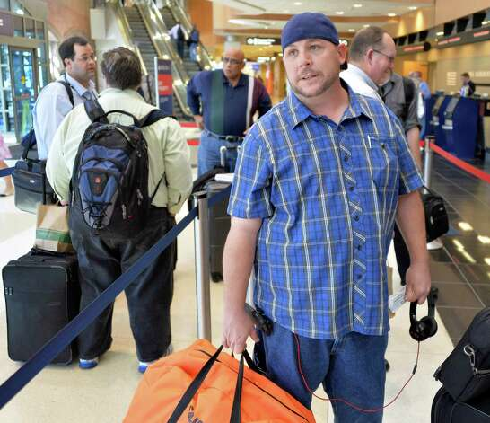 Stranded traveler Brian Campbell of Phoenix, Arizona, in line at a ticket counter at Albany Airport after a fire at a suburban air traffic control center in Illinois disrupted flights Friday Sept. 26, 2014.   (John Carl D'Annibale / Times Union) Photo: John Carl D'Annibale