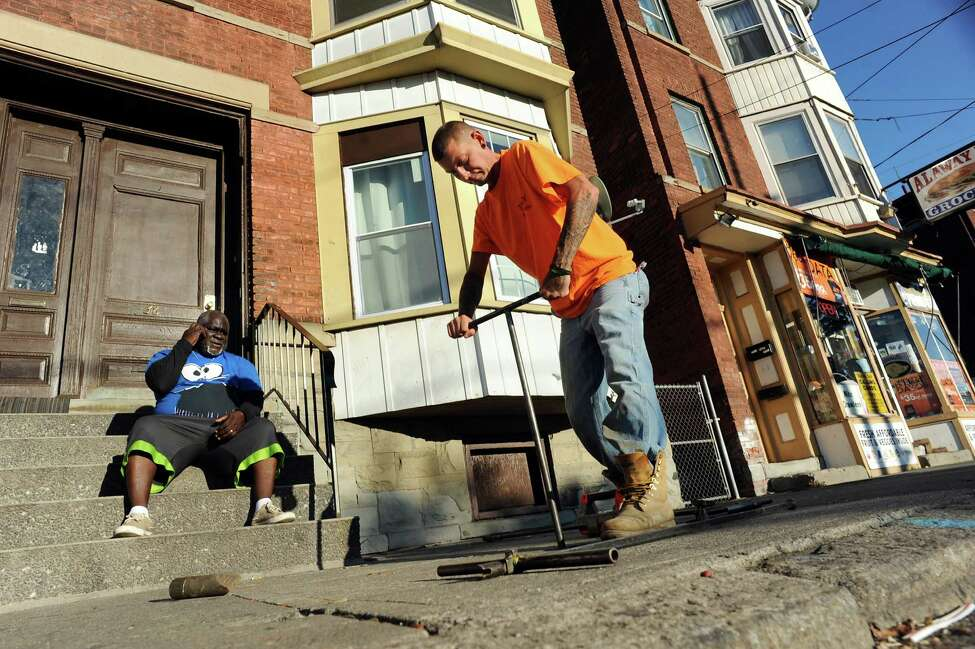 Butch Hull of the City of Troy Water Dept., center, works to turn on the water for Mac Henderson, left, on Friday, Sept. 26, 2014, in Troy, N.Y. Henderson and his family were without water last week because his landlord didn't pay the bill. (Cindy Schultz / Times Union)