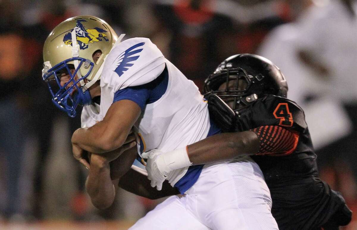 Elkins Kahlif Smith (24) is tackled by Texas City's Da'Quan Thompson (4) in a high school football game on September 26, 2014 at Stingaree Stadium in Texas City, TX .