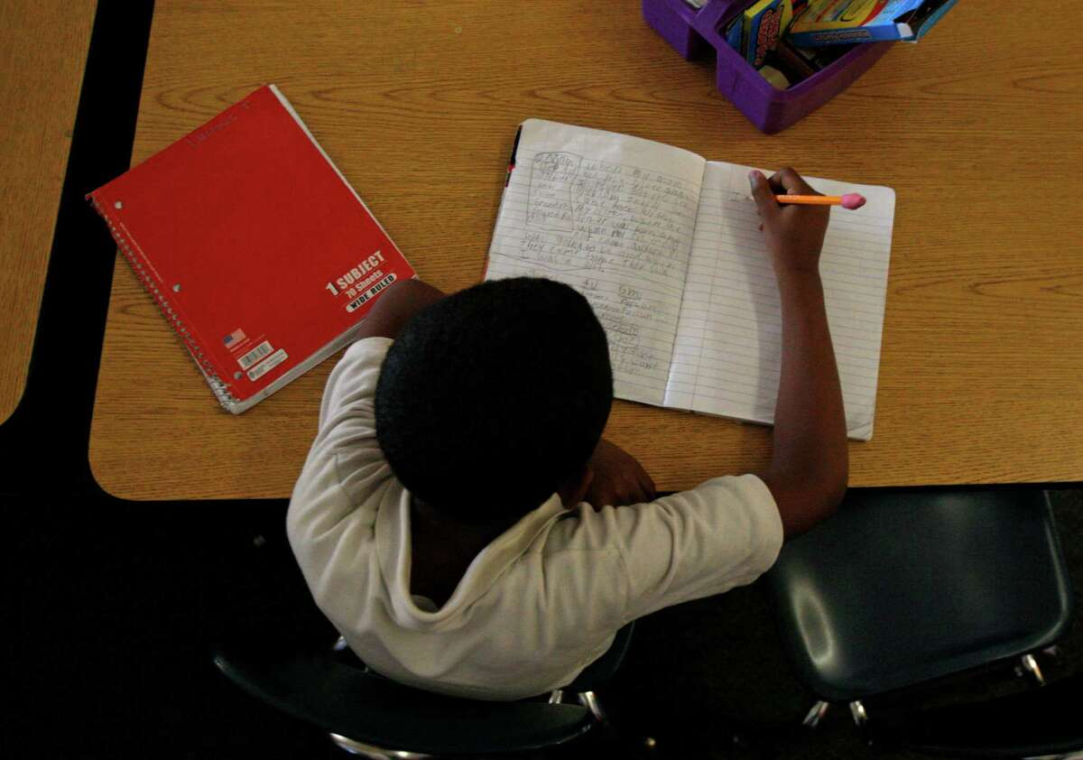 A student writes in his notebook at Garfield Elementary School in Oakland.