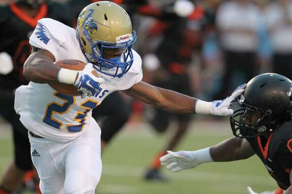 Elkins' Xavier Barnes stiff-arms a Texas City defender during Friday night's game at Stingaree Stadium in Texas City.