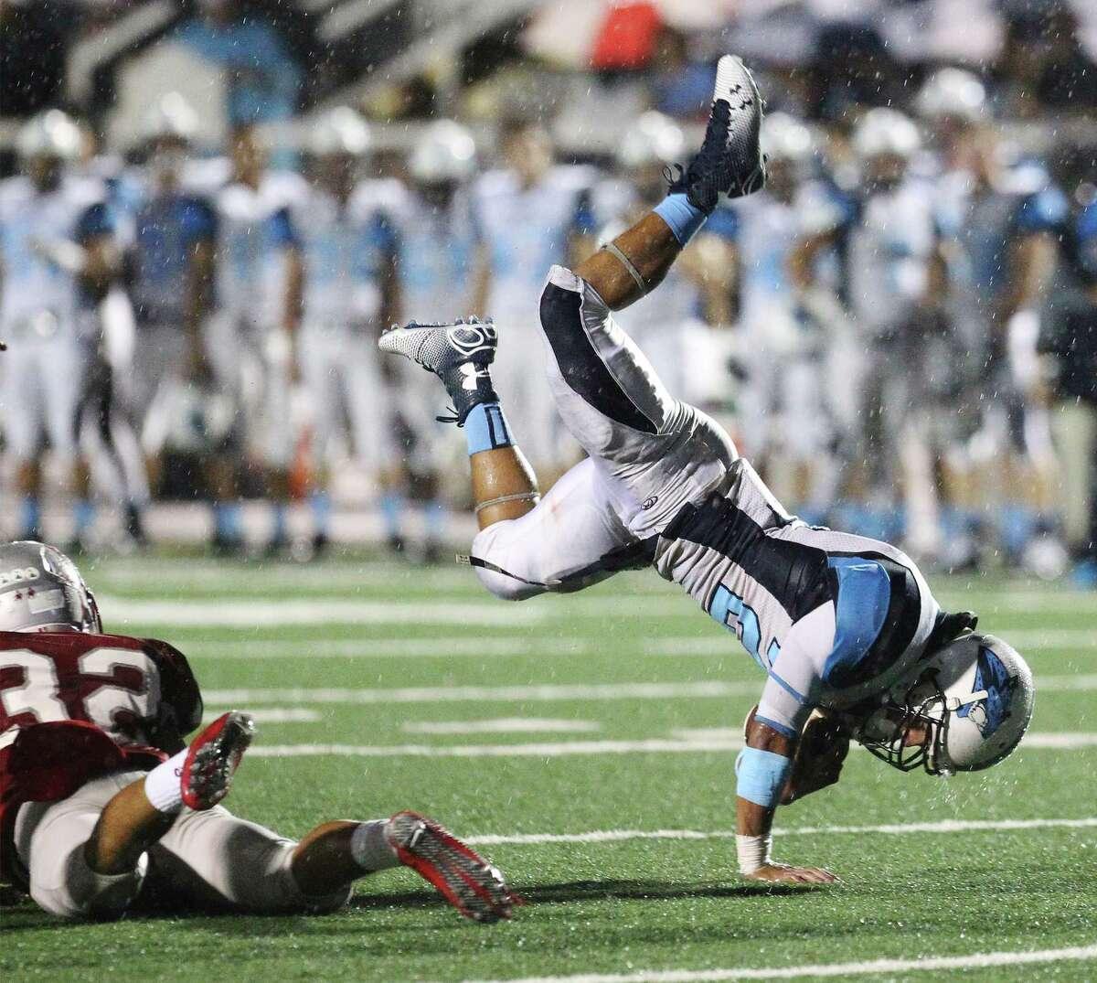 Johnson's R.J. Espinoza (21) gets tripped up by Lee's Adrian Vargas (32) at Comalander Stadium on Friday, Sept. 26, 2014. (Kin Man Hui/San Antonio Express-News)