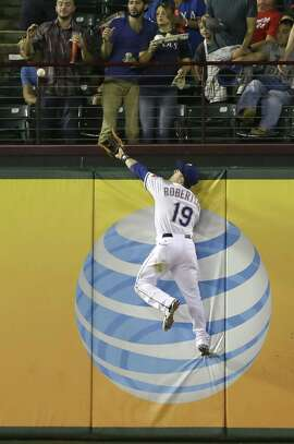 Texas Rangers left fielder Daniel Robertson (19) cannot reach the solo home run by Oakland Athletics Josh Reddick, not shown, during the fourth inning of a baseball game in Arlington, Texas, Friday, Sept. 26, 2014. The Athletics won 6-2. (AP Photo/LM Otero)