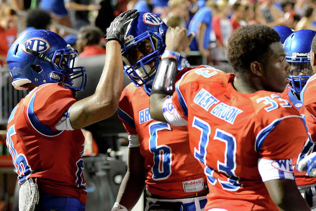 West Brook Bruins Delano Hawthorne, 26, and D'angelo Godfrey, 33, congratulate Innis Gaines, 6, after an interception and nice gain during the match up against the North Shore Mustangs at the Carroll Thomas Stadium September 26, 2014. Photo by Drew Loker. Photo: Drew Loker / ©2014. www.DrewLoker.com