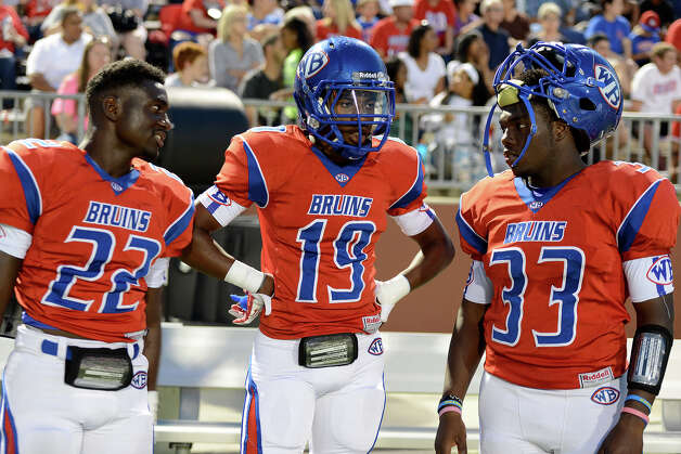 West Brook Bruins Isaac Cheatham, 22, Nate Paker, 19, and D'angelo Godfrey, 33, discuss the game against the North Shore Mustangs at the Carroll Thomas Stadium September 26, 2014. Photo by Drew Loker. Photo: Drew Loker / ©2014. www.DrewLoker.com