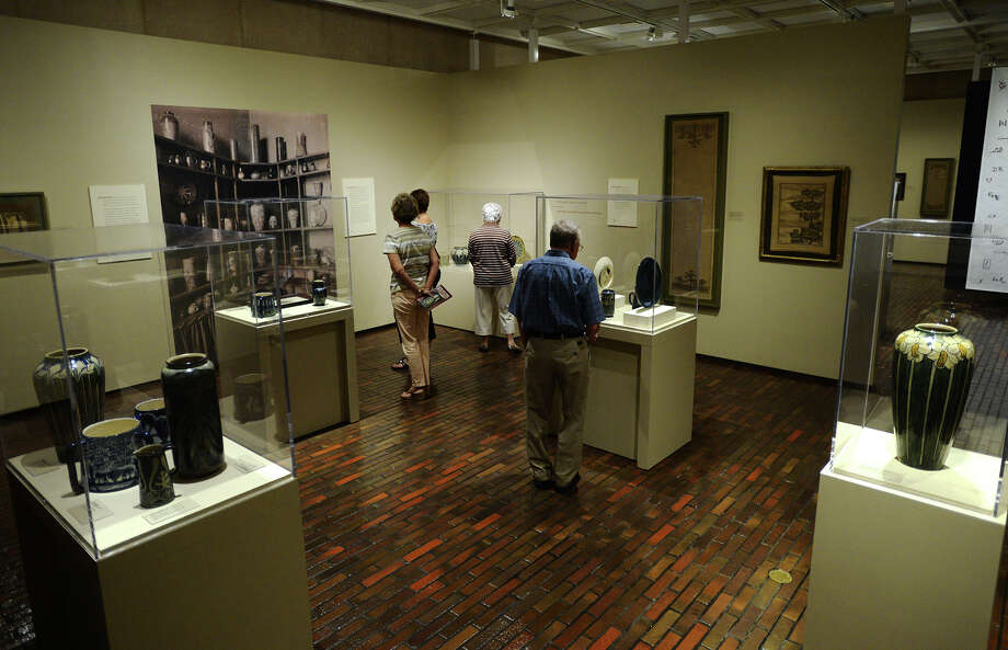 """People examine the pieces inside the Newcomb Pottery Enterprise exhibit at the Stark Museum on Saturday morning. The Stark Museum of Art in Orange participated in the Smithsonian Day event Saturday, granted those with tickets printed from the Smithsonian magazine free admission to the grounds. The event coincided with a new exhibit from the Smithsonian, """"Women, Art and Social Change: The Newcomb Pottery Enterprise."""" Photo taken Saturday 9/27/14 Jake Daniels/@JakeD_in_SETX Photo: Jake Daniels / ©2014 The Beaumont Enterprise/Jake Daniels"""