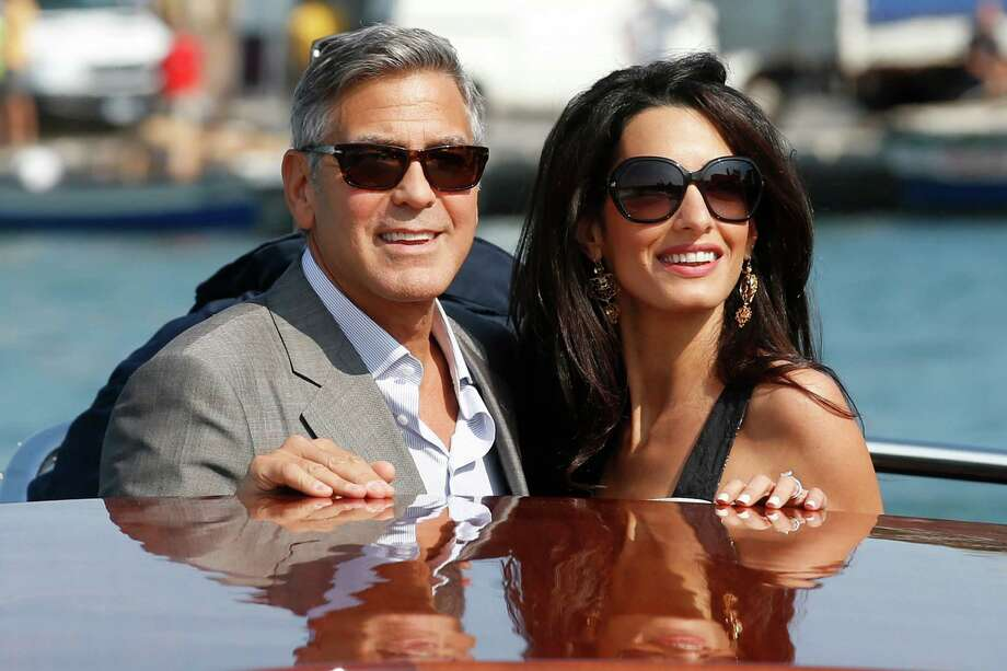 George Clooney, left, and Amal Alamuddin arrive in Venice, Italy, Friday, Sept. 26, 2014. Clooney, 53, and Alamuddin, 36, are expected to get married this weekend in Venice, one of the world's most romantic settings. Photo: Luca Bruno, Associated Press / AP