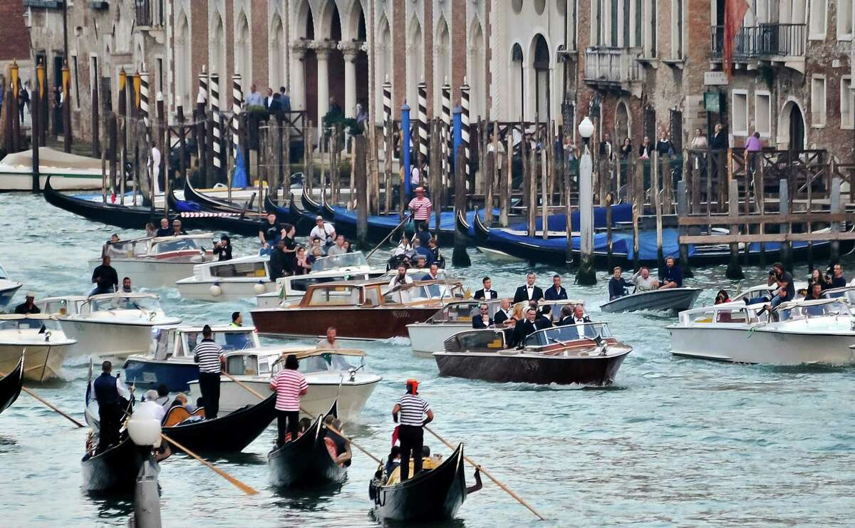 The boat carrying actor George Clooney and his guests cruises in front of media boats in the Grand Canal on its way to the Aman hotel ahead of his wedding in Venice, Italy, Saturday, Sept. 27, 2014.