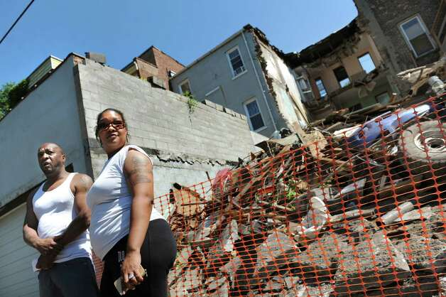 Homeowners Rasheem Robinson, left, and his wife, Jamie Robinson, talk about the building next door on Saturday, July 5, 2014, in Albany, N.Y. They had to leave their home because the building at 162 Clinton Ave. partially collapsed. (Cindy Schultz / Times Union) ORG XMIT: MER2014070515425709 Photo: Cindy Schultz