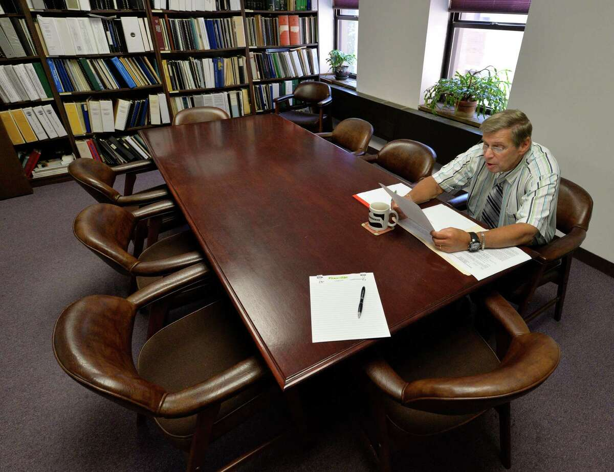 Hearing officer Jay Sherman sits alone while reading legal documents for a Rensselaer County Industrial Development Agency public hearing Tuesday morning Sept. 9, 2014 in Troy, N.Y. It's not uncommon for public meetings of IDAs to go unattended, and unnoticed. (Skip Dickstein/Times Union)