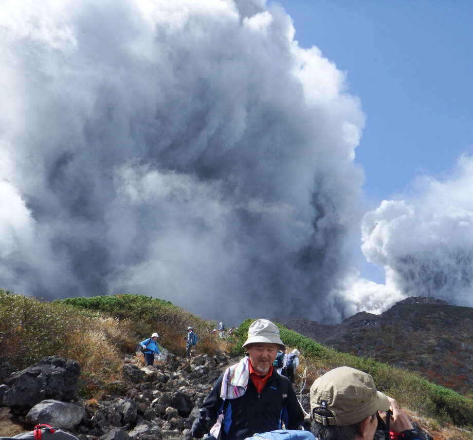 Mountain climbers descend Mount Ontake as they flee the volcano in Japan. The eruption left at least 40 injured, with some people missing. Photo: Associated Press / Kyodo News