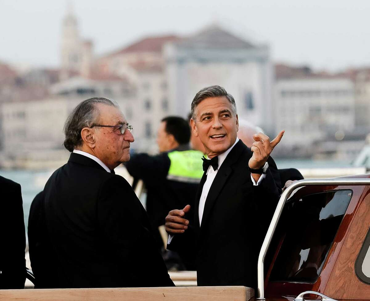 Actor George Clooney, right, talks to Ramzi Alamuddin, father of her fiancee Amal Alamuddin, on a boat carrying them to the Aman hotel ahead of his wedding in Venice, Italy, Saturday, Sept. 27, 2014. (AP Photo/Luca Bruno)