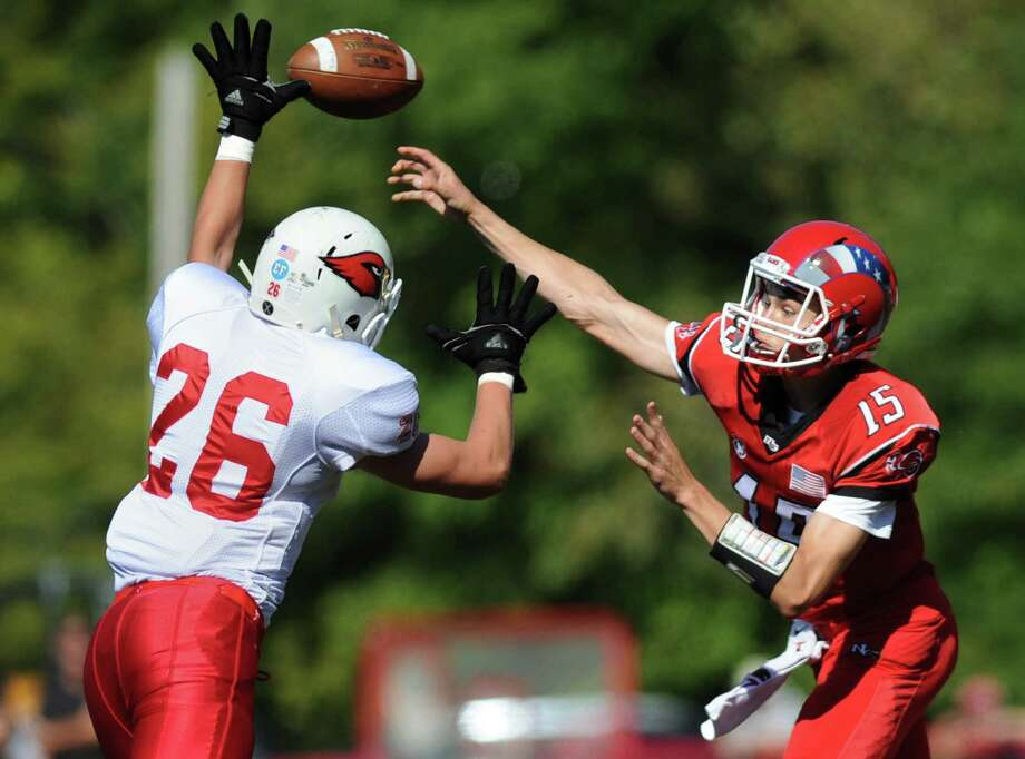Greenwich's James Kitt (26) defends a pass from New Canaan quarterback Michael Collins (15) in New Canaan's 35-20 win over Greenwich in the high school football game at New Canaan High School in New Canaan, Conn. Saturday, Sept. 27, 2014. Photo: Tyler Sizemore / The News-Times
