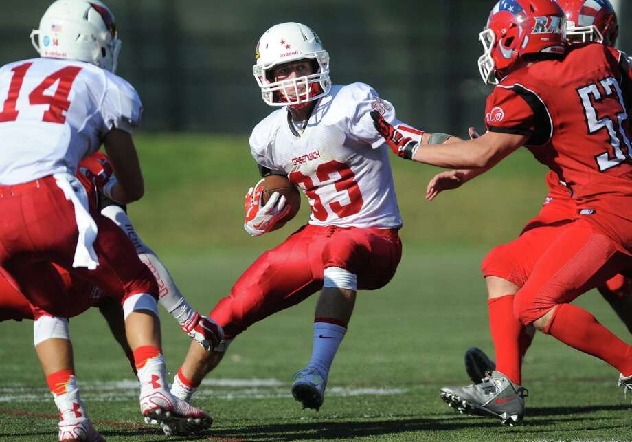 Greenwich's Luke Bienstock (33) weaves between teammate Walker Manning (14) and New Canaan defender Chris Keeffe (52) in New Canaan's 35-20 win over Greenwich in the high school football game at New Canaan High School in New Canaan, Conn. Saturday, Sept. 27, 2014. Photo: Tyler Sizemore / The News-Times