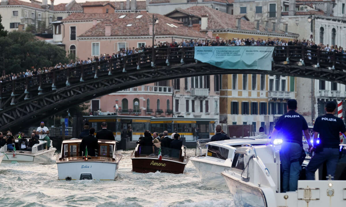 The boat Amore (center) carries actor George Clooney along the Grand Canal under the Academia Bridge to his wedding.