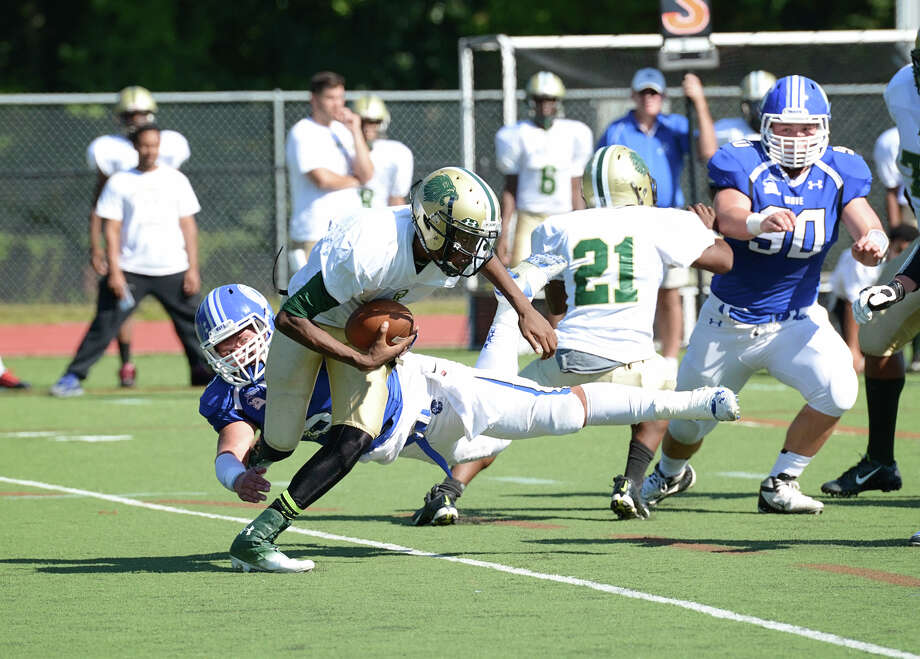 Darien's George Reed (5) goes after Bassick ball carrier Eric Jones (1) during the second quarter of the football game at Darien on Saturday, Sept. 27, 2014. Photo: Amy Mortensen / Connecticut Post Freelance