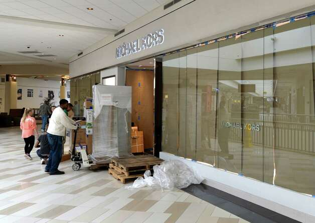 Workers move in items in to the new Michael Kors store at the Crossgates Mall Monday morning Sept. 22, 2014, Albany, N.Y.        (Skip Dickstein/Times Union) Photo: SKIP DICKSTEIN / 00028689A