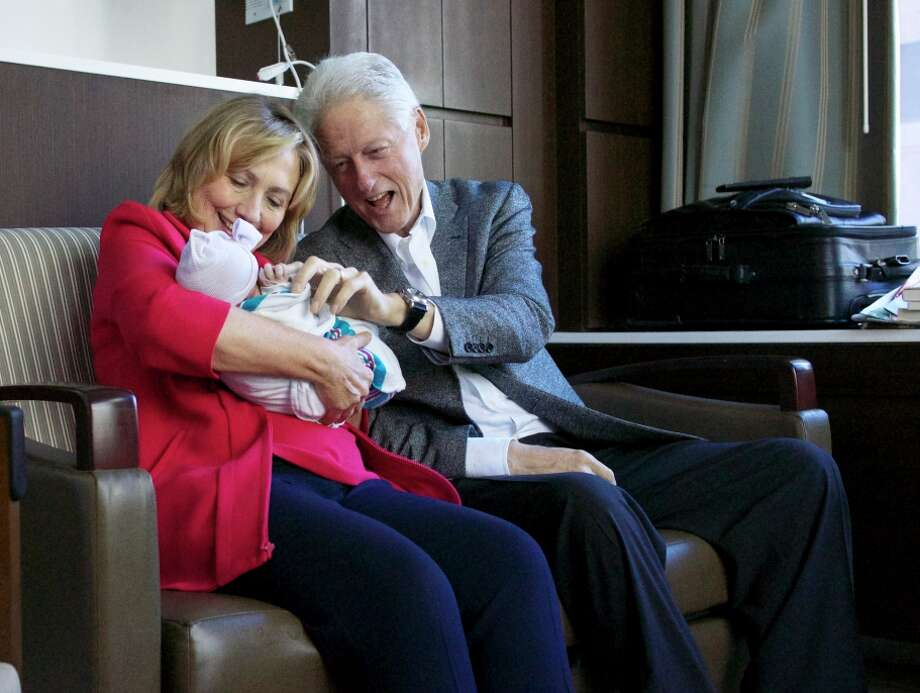 Former Secretary of State Hillary Rodham Clinton and former President Bill Clinton delight in granddaughter Charlotte. Photo: Associated Press / Office of President Clinton