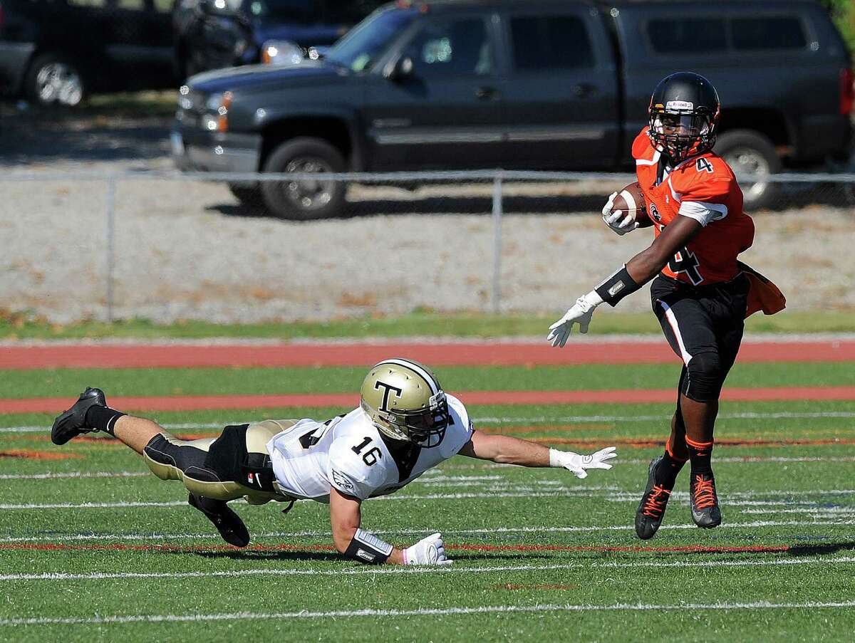 Stamford's Guyeens Antoine carries the ball as he avoids Trumbull's Niko Principi during Saturday's game at Stamford High School on September 27, 2014.