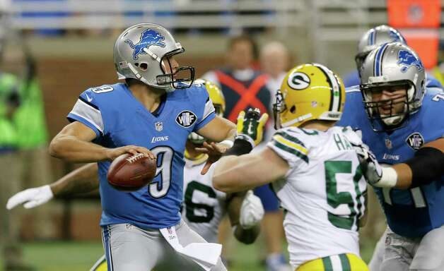 Detroit Lions quarterback Matthew Stafford, under pressure from Green Bay Packers inside linebacker A.J. Hawk, looks downfield during the first half of an NFL football game in Detroit, Sunday, Sept. 21, 2014. (AP Photo/Carlos Osorio) ORG XMIT: DTF102 Photo: Carlos Osorio / AP