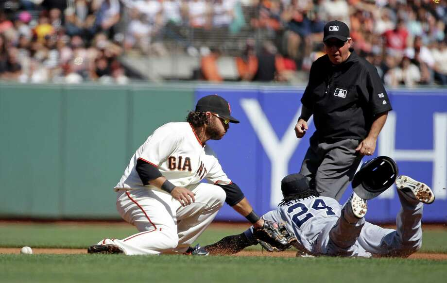 San Diego Padres' Cameron Maybin, right, slides safely into second base as San Francisco Giants shortstop Brandon Crawford, left, makes a tag in the fourth inning of their baseball game Saturday, Sept. 27, 2014, in San Francisco. Maybin reached second on a fielding error by Giants right fielder Juan Perez. In the background is second base umpire Tom Hallion. (AP Photo/Eric Risberg) Photo: Eric Risberg / Associated Press / AP