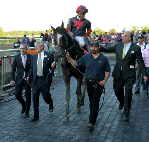 Tonalist with jockey Joel Rosario is lead to the winner's circle by owner Robert Evans, second from left and trainer Cristophe Clement, right after winning the 96th running of The Jockey Club Gold Cup Saturday evening Sept. 27, 2014, at Belmont Park in Elmont, N.Y.    (Skip Dickstein/Times Union) Photo: SKIP DICKSTEIN