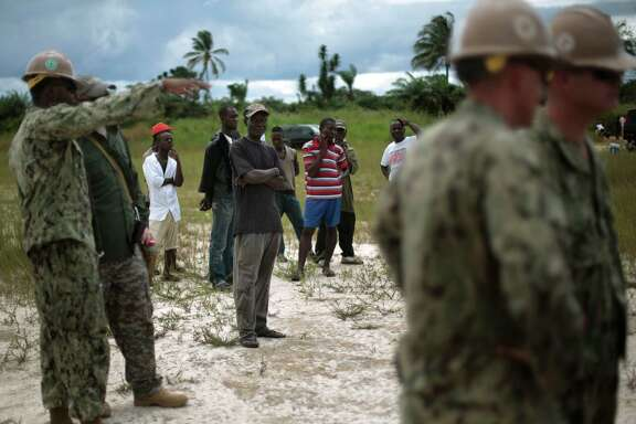 Local workers look on as  a team or U.S. Navy engineers prepares the ground for  a 25-beds medical facility they are building next to the airport in Monrovia, Liberia, Saturday Sept. 27, 2014. Six months into the world's worst-ever Ebola outbreak, and the first to happen in an unprepared West Africa, the gap between what has been sent by other countries and private groups and what is desperately needed is huge. Even as countries try to marshal more resources to close the gap, those needs threaten to become much greater, and possibly even insurmountable. (AP Photo/Jerome Delay)